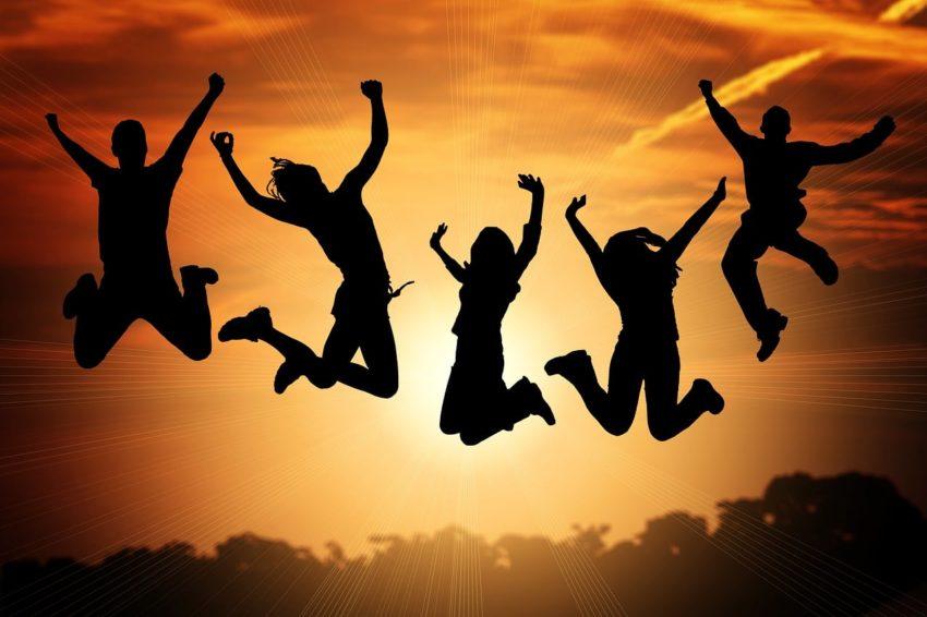 Osoby skaczące podczas zachodu słońca